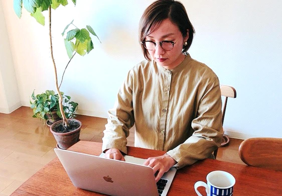 ライター野中真規子が片付いた部屋で机に座りノートパソコンを操作している画像