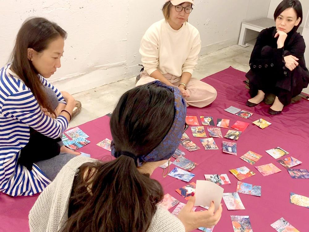 女性4人が床に車座になって座り、占い・カードについてディスカッションしている画像